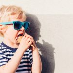 Cute kid boy with sunglasses eating ice cream at sunset. Boy looking at empty space.